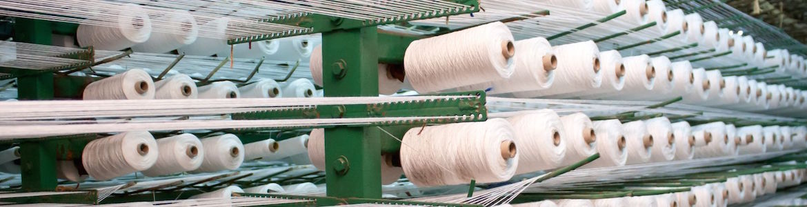 factory large group of bobbin thread cones on a warping machine in a textile mill